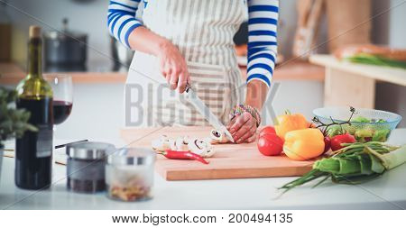 Young woman cutting vegetables in kitchen at home.