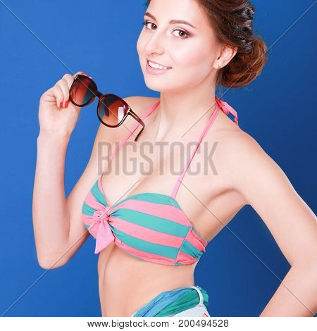 Young brunette posing in swimsuit while isolated on blue background.