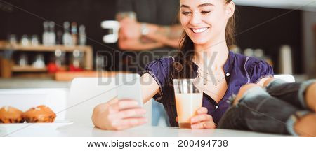 Young woman using smartphone sitting in kitchen.