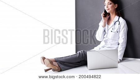 Young woman doctor sitting talking on phone.