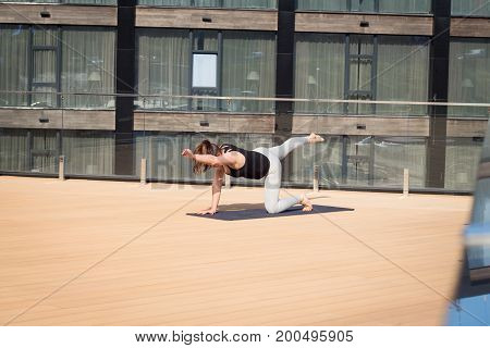 sport woman doing stretching yoga exercise on hotel roof