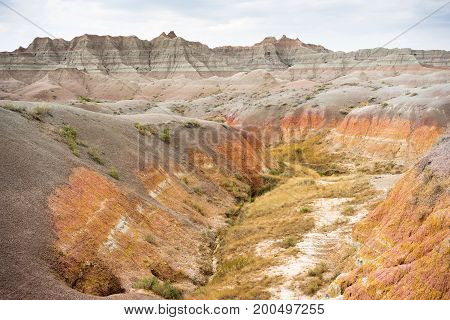 Clouds allow the sun to light rock formations in the South Dakota Badlands