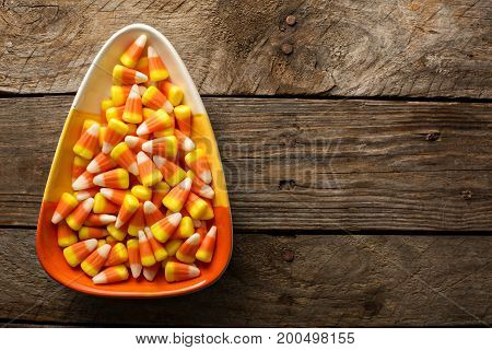 Candy corn in a bowl Halloween background overhead shot with copy space