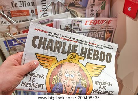 PARIS ENGLAND - MAY 14 2017 : A hand holding Charlie Hebdo over newsstand background in Paris. Charlie Hebdo is a French satirical weekly magazine featuring cartoons reports polemics and jokes.