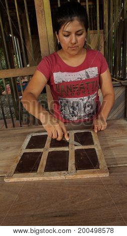 Puerto Quito, Pichincha / Ecuador - August 17 2017: Young latin woman removing chocolate blocks from handmade wooden molds with a knife