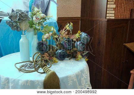 Still-life Of Artificial Flowers And Glass Bottles