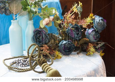 Still Life Of Artificial Flowers And Glass Bottles