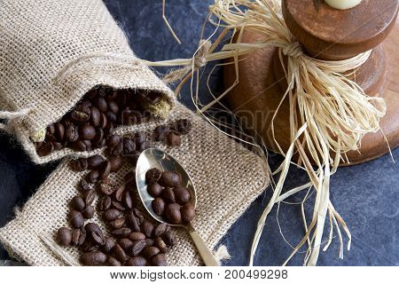 Coffee beans in a hessian bag with a candle stick and spoon.