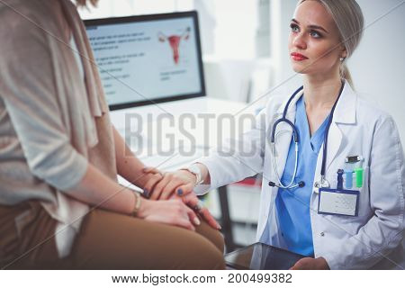 Doctor and patient discussing something while sitting at the table. Medicine and health care concept. Doctor and patient.