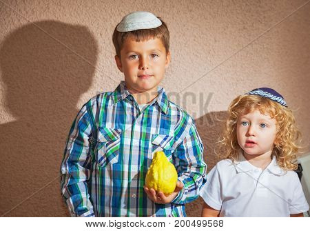 Sukkot in Israel. Two beautiful Jewish boy in skull-caps. The elder brother holds a ritual fruit - Etrog