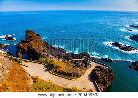 Picturesque yellow and  black rocks at coast of Atlantic. Fabulous travel on the volcanic island of Madeira. Concept of exotic and ecological tourism