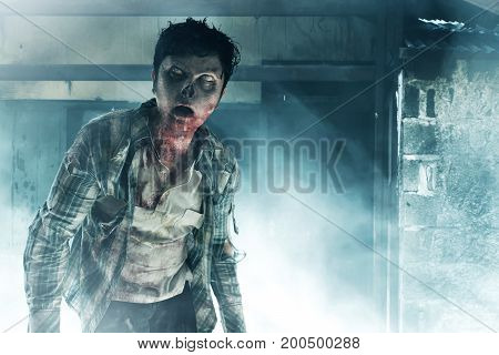 Scary zombie walking on old haunted house