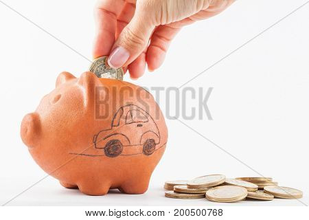 Close up of a woman saving money into a traditional clay piggy bank for a car