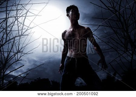 Scary zombie in spooky forest at night
