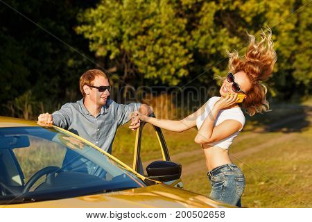 Couple in love. Road Trip. The guy is standing at the open door of the car. The girl is talking on the cell phone.