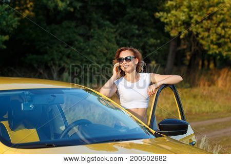 Young attractive girl talking on cell phone. She stands at the open door of the car. Stopover. Call the tow truck.