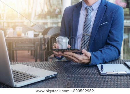 Executive businessman working analyzing investment using tablet and laptop business outdoor analyzing financial figures professional investor.
