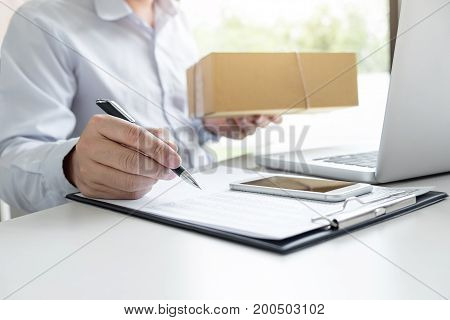 Man seller write a order product to prepare for delivery to customers customer service network connection market technology on global Order online for customer convenience.