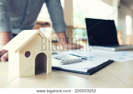 Businessman looking to sign a home insurance policy on home loans and pointing investment chart graph loan documents calculating installment payment Real Estate concept.