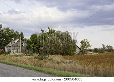 Landscape scene of an old abandoned house in an overgrown field of trees and shrubs on a country road in Maine, USA on a sunny day with clouds in September.