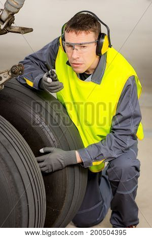 airport worker mechanic service maintenance chassis tire