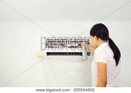 Woman cleaning air conditioning by foam cleaning agent.