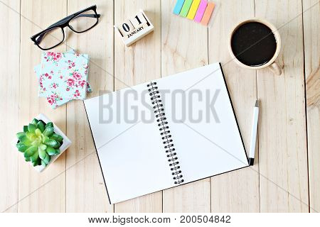 Still life, business office supplies or new year concept : Top view of working desk with blank notebook with pen, coffee cup, colorful note pad, cube calendar and eyeglasses on wooden background