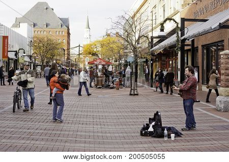 Burlington, Vermont - November 11, 2013 - Wide view of a street artist/busker playing his guitar and harmonica for the crowds of people on the main street of the