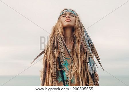 fashion model portrait outdoors. boho style young woman with headdress made of feathers