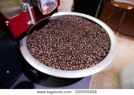 Arabica coffee beans in coffee machine roasting process.Coffee roasters machine. roasted coffee beans in spinning cooler professional machine.selective focus