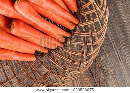 Carrot in wicker on wooden surface, GMO free