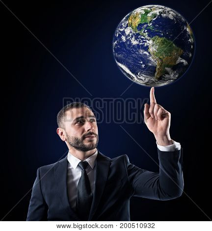 Successful businessman holds the world with a finger. World provided by NASA