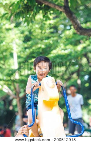 An Asian Boy Is Playing A Rocking Horse In An Outdoor Playground.image With Grain.