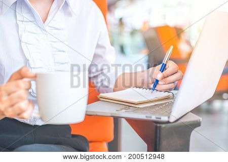 The Hand Of A Business Woman Writing With A Pen In Notepad In The Office.