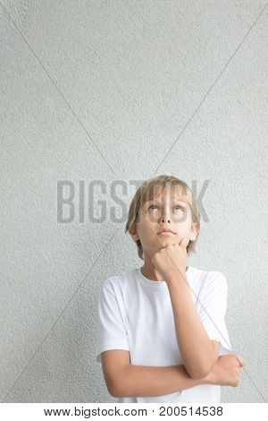 Portrait of thoughtful boy with crossed arms standing near grey wall and looking up
