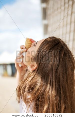 Young cheerful girl is eating ice cream on walk, on promanade.