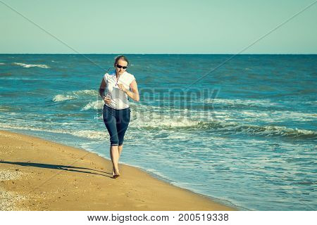 A woman in a white sports jacket is Jogging on the beach. The concept of a healthy lifestyle in nature.