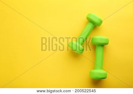 New green dumbbells on the yellow background