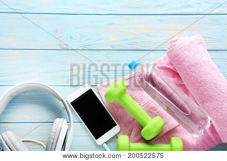 Green Dumbbells With Towel, Bottle And Smartphone With Headphones On Wooden Table