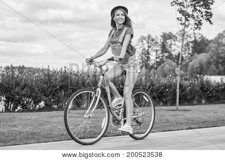 Black and white shot of a beautiful happy young woman enjoying riding bicycle at the park happiness emotions youth freedom carefree hipster bicyclist.