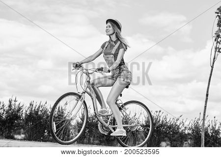 Monochrome shot of a beautiful young happy woman smiling joyfully while riding bicycle at the local park happiness relaxation activity sportswoman hipster lifestyle travelling concept.