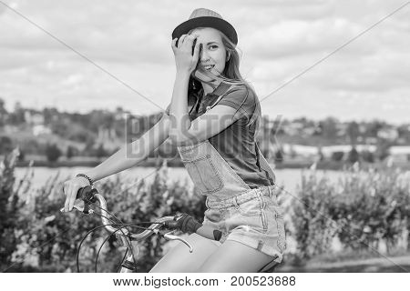 Monochrome shot of a beautiful young woman riding bicycle at the park fixing her hair smiling joyfully romantic beauty femininity sensuality recreation lifestyle concept.