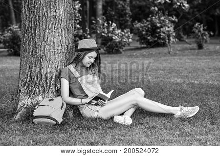 Monochrome shot of a young beautiful woman relaxing at the local park sitting on the grass under the big tree enjoying reading a book smiling happily copyspace studying education holidays hobby.