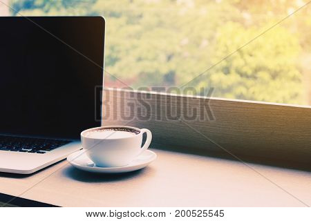 Coffee and laptop on desk bar in cafe with drink in morning.