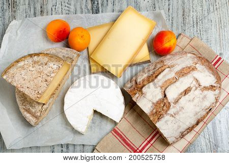 Different french cheeses with a bread and apricots