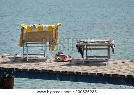deckchair at lake on wooden dock for holidays