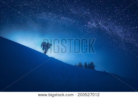 Photographer who take a picture of starry sky in a night winter valley.