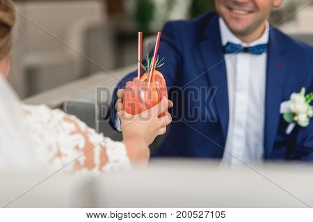 People hold in hands glasses with orange cocktail. wedding party. Bridesmaids toasting with a cocktail