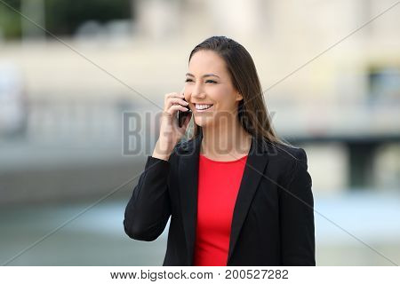 Smiley executive talking on a mobile phone walking on the street
