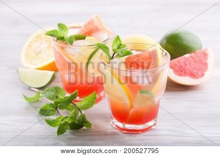 Homemade cold citrus lemonade on a light wooden background